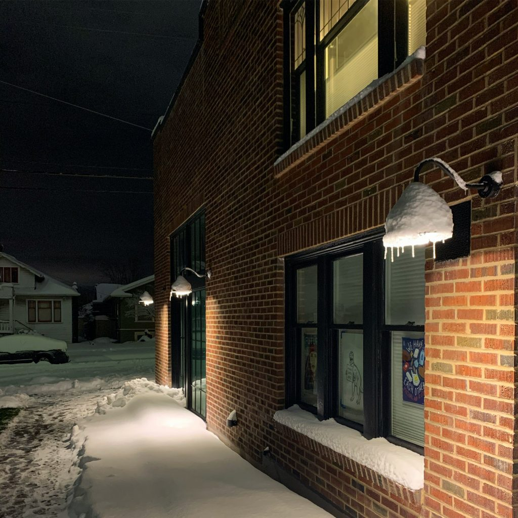 The south side of the building at at night, with glowing light and icicles hanging down.